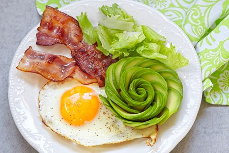 eggs and bacon: Fried Egg, Bacon and Avocado Rose. Low carb high fat breakfast Stock Photo