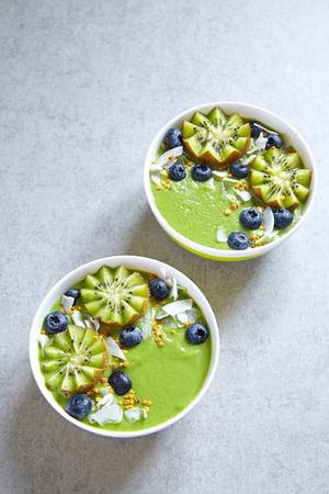 jugo verde: el desayuno tazón batido verde cubierto con kiwi, arándanos, coconutflake y polen de abeja Foto de archivo