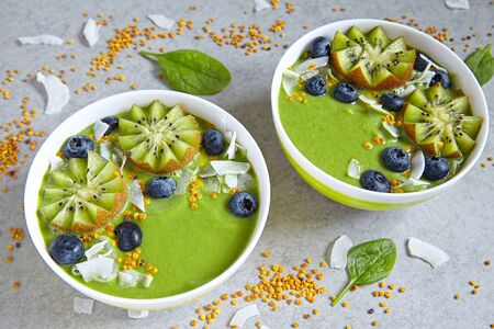bee pollen: breakfast green smoothie bowl topped with kiwi, blueberry, coconutflake and bee pollen