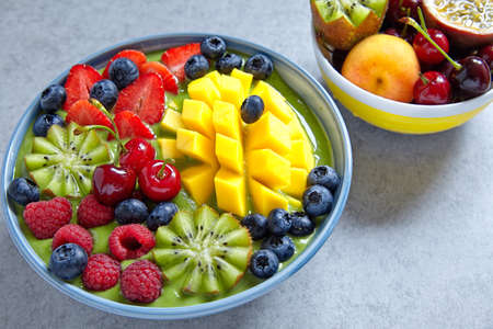 breakfast bowl: breakfast green smoothie bowl topped with fruits and berries Stock Photo