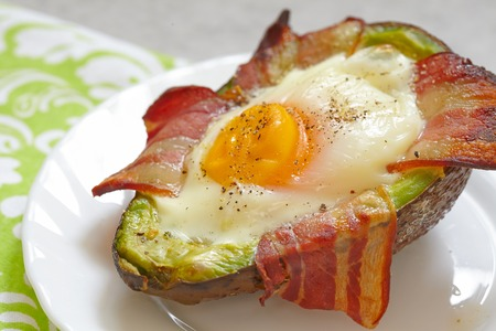 garnish: Avocado Egg Boats with bacon. Low carb high fat breakfast Stock Photo