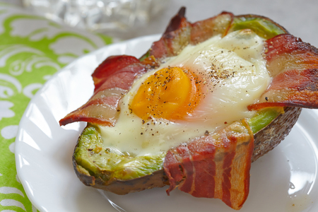 Avocado Egg Boats with bacon. Low carb high fat breakfast 스톡 콘텐츠