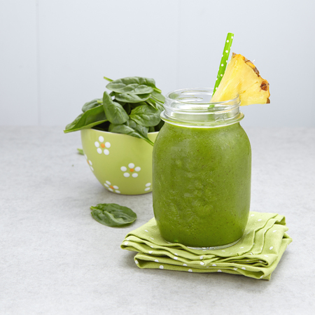 Spinach green smoothie topped with a pineapple slice