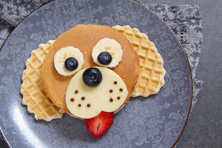 Funny dog pancake with berries for kids breakfast