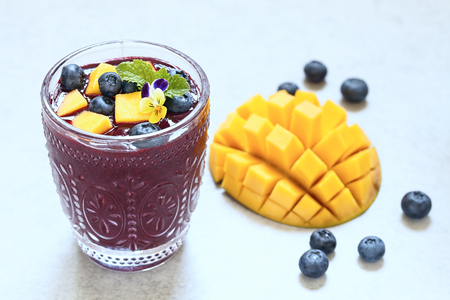 clean food: Fresh smoothie with mango and blueberry topping
