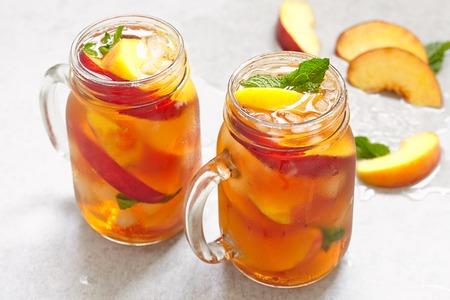 Mason jars of peach tea with ice Stock Photo
