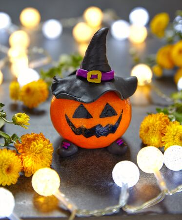 Funny Halloween pumpkin tangerine with black witches hat Stock Photo