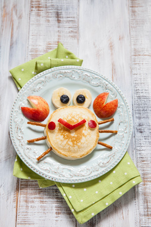Funny breakfast for child. Pancake crab with apple. Stock Photo