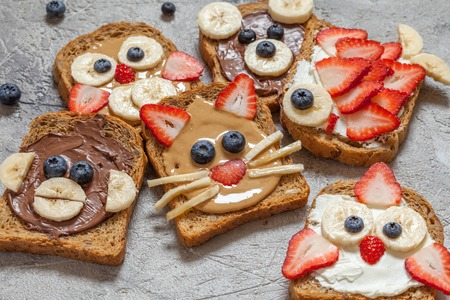 spreads: Funny animal faces toasts with spreads, banana, strawberry and blueberry