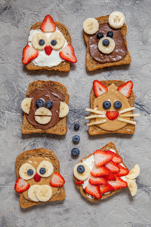 pb: Funny animal faces toasts with spreads, banana, strawberry and blueberry
