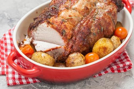 Sin hueso de cerdo asado de lomo con patatas y tomates Foto de archivo - 63569168
