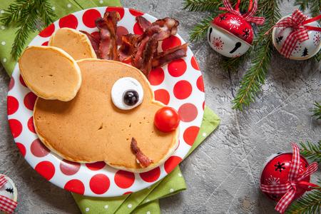 Christmas fun food for kids. Rudolph reindeer pancake for breakfast 免版税图像