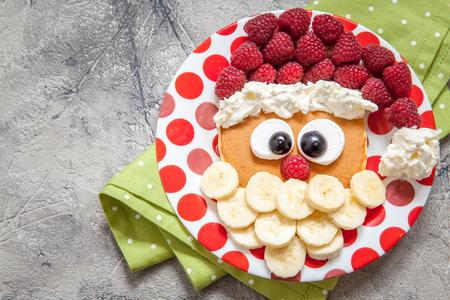 niños comiendo: Navidad Papá panqueque con frambuesa y plátano para el desayuno niño