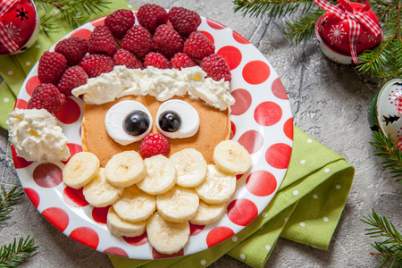 子供の朝食にバナナとラズベリーのクリスマス サンタ パンケーキ 写真素材