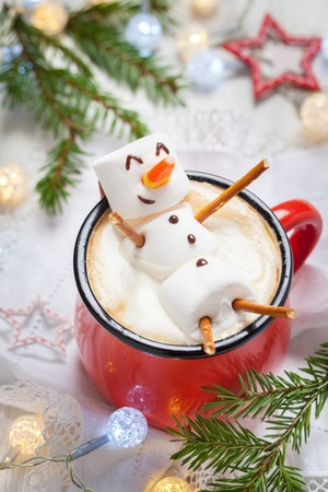 Red mug with hot chocolate with melted marshmallow snowman Zdjęcie Seryjne - 64818083