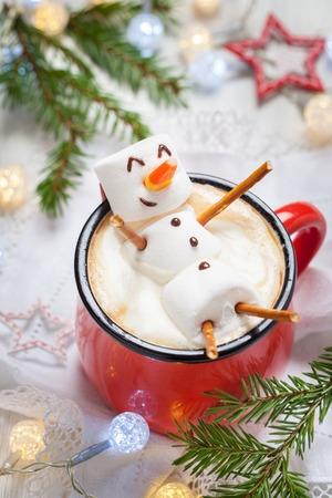 Taza roja con chocolate caliente con muñeco de nieve derretida melcocha