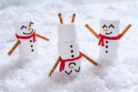 Happy funny marshmallow snowmans are having fun in snow Banque d'images