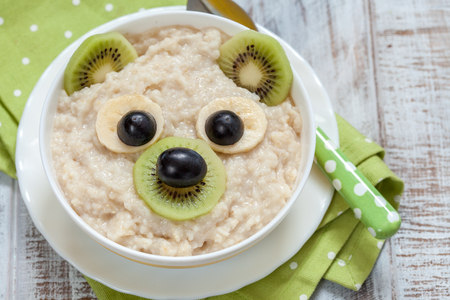 Kids breakfast oatmeal porridge with fruits and nuts Stock Photo