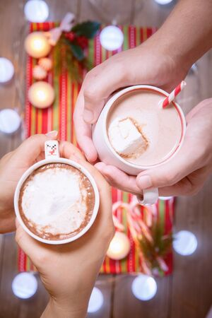 comfort food: Two mugs in a hands with hot chocolate. Top view Stock Photo