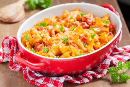 Pasta casserole with bacon, ham, cheese and tomato sauce Stock Photo