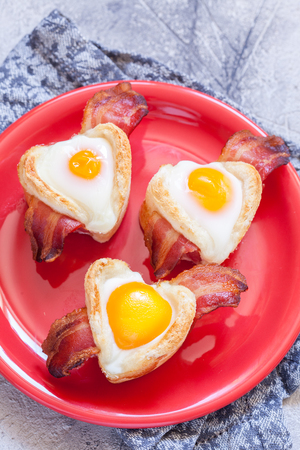 Baked egg breakfast with bacon heart shape for Valentine day Stock Photo
