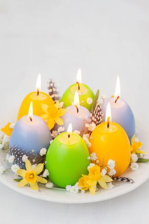 easter candle is burning: Colorful easter egg candles and flowers