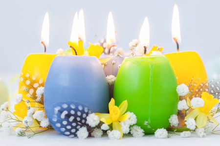 Colorful easter egg candles and flowers