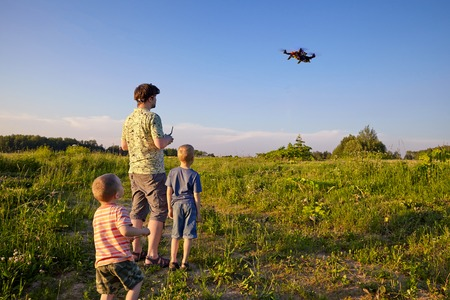 Father and son controls RC drone in the sky