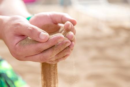 Hands strew sand running Standard-Bild