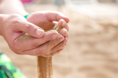 strew: Hands strew sand running Stock Photo