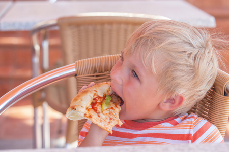 Child eats pizza in cafe, tinted photo.