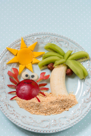 children crab: Fruit dessert for kid child with kiwi, banana and pear Stock Photo