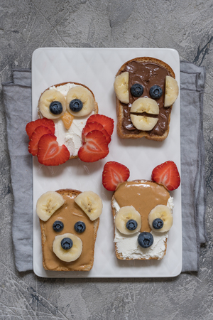 bear berry: Funny animal faces toasts with spreads, banana, strawberry and blueberry