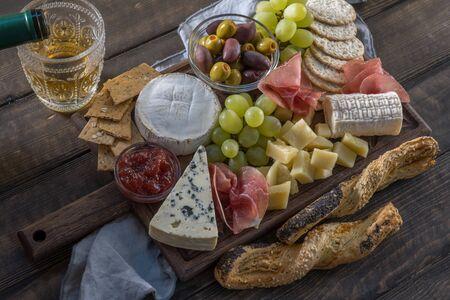 ブドウ、ジャム、生ハムと木製の背景にクラッカーを添えてチーズ プレート