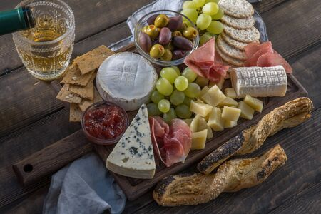 Cheese plate served with grapes, jam, prosciutto and crackers on a wooden background Stok Fotoğraf