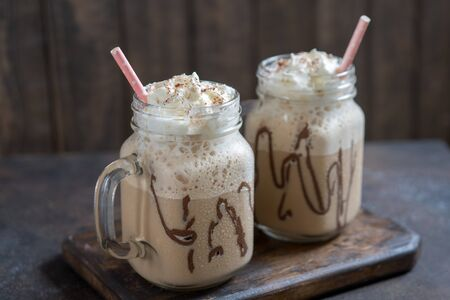 Cold coffee drink frappe frappuccino with whipped cream and chocolate syrup