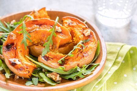 Roasted pumpkin with pecan nuts and arugula. Stock Photo
