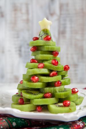 Healthy dessert idea for kids party - funny edible kiwi pomegranate Christmas tree 스톡 콘텐츠