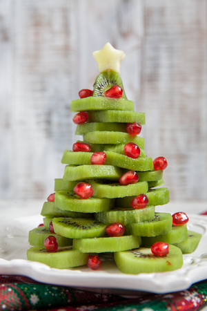 Healthy dessert idea for kids party - funny edible kiwi pomegranate Christmas tree Фото со стока
