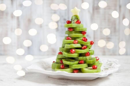 Healthy dessert idea for kids party - funny edible kiwi pomegranate Christmas tree 스톡 콘텐츠