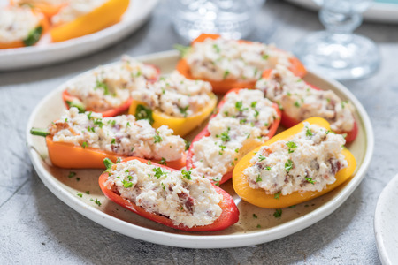 Colorful mini peppers stuffed with cheese, bacon and herbs
