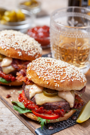 Two cheeseburgers on sesame buns with jalapeno on a rustic wood table