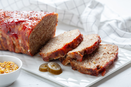 Bacon Wrapped Ground Beef Meatloaf with Cabbage and Bulgur Фото со стока
