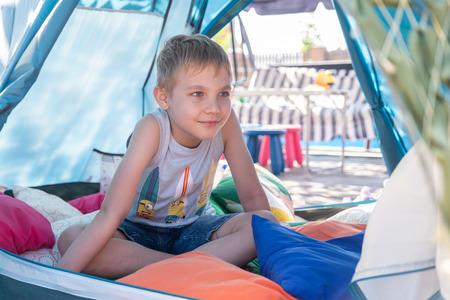 Portrait of cute boy inside tent at backyard