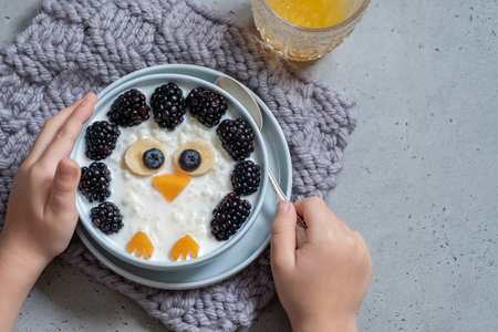 Funny kids breakfast porridge with berries
