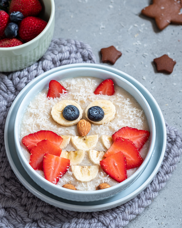 Kids breakfast oatmeal porridge with berries and nuts