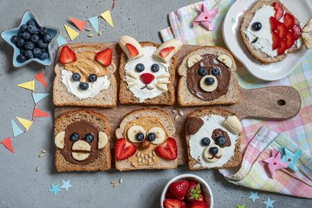 Animal faces toasts with spreads, banana, strawberry and blueberry