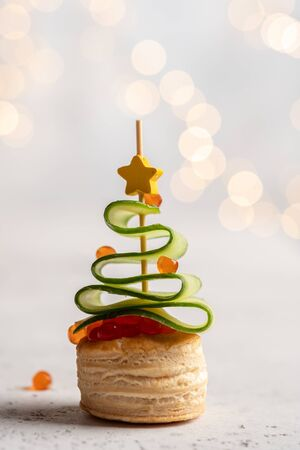 Christmas tree canape with cucumber slice, salmon pate and red caviar Stockfoto