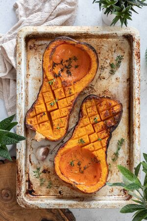 Tray with roasted butternut squash pumpkin and herbs
