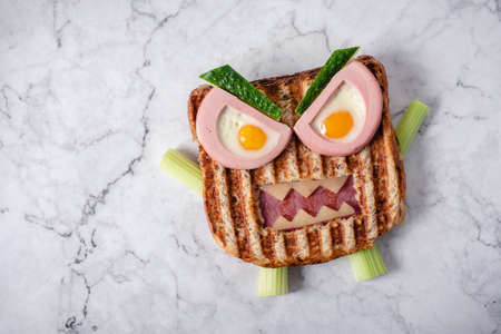 Monster sandwich with sausage, eggs and cheese on plate. 版權商用圖片